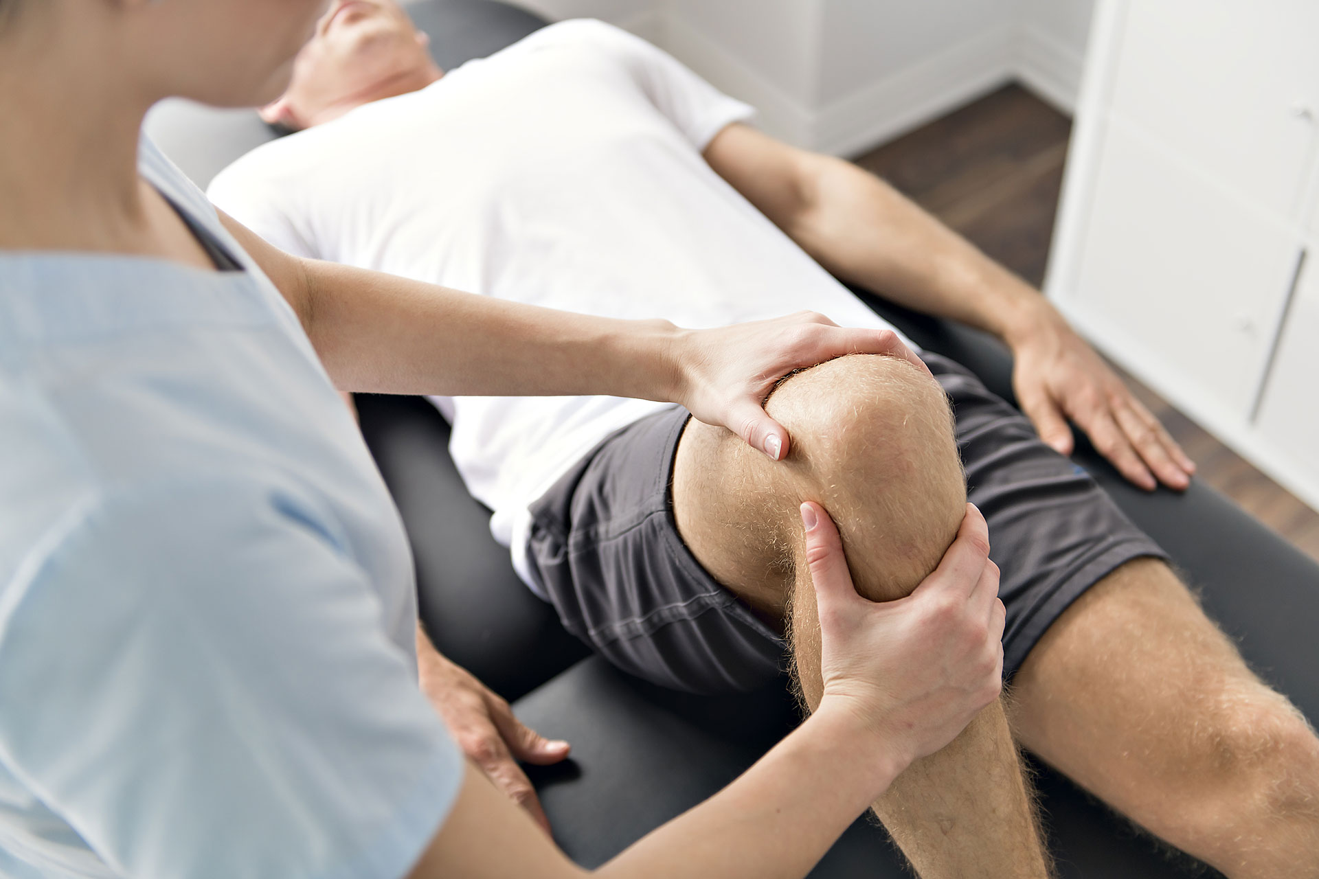 Practitioner performing sports medicine, chiropractic, physical therapy on a patients knee.