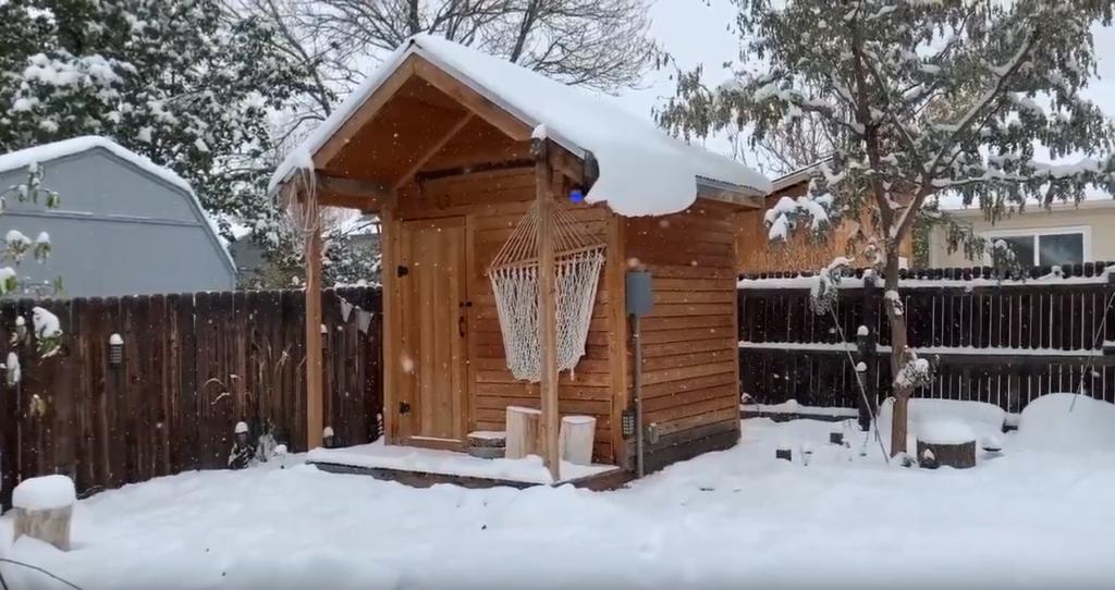 Sauna in snowy backyard.